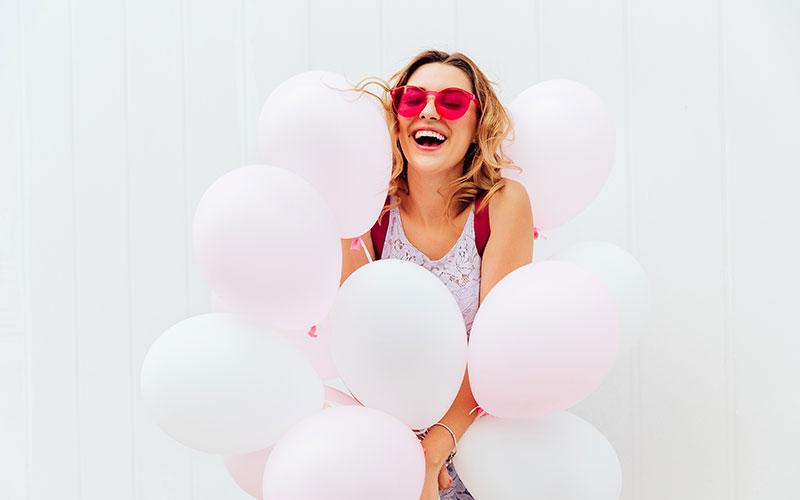 junge frau mit roter sonnenbrille am lachen und hält luftballons in der hand